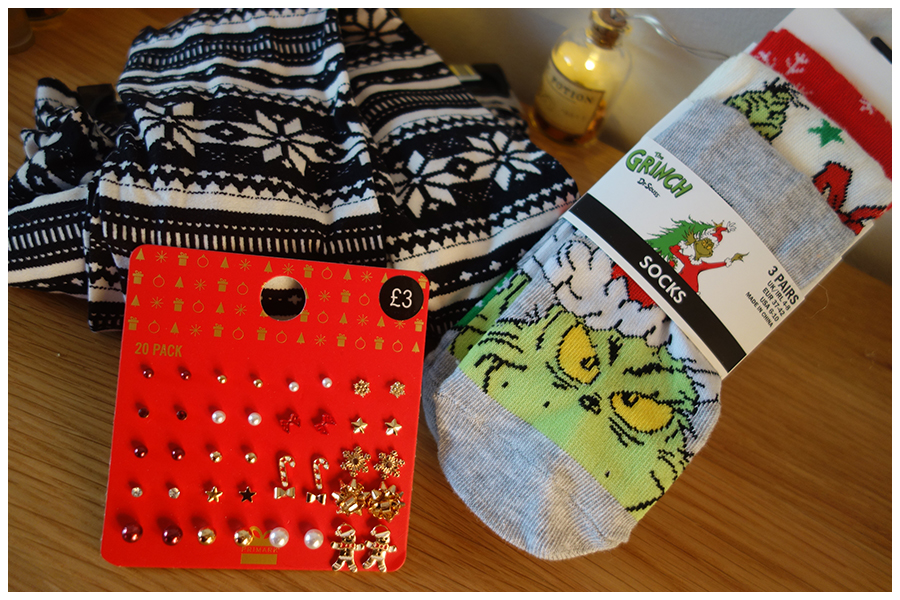 The three items of clothing I boought, left to right is a pair of black and whit epatternes cosy leggings, a pack of twenty gold and red christmas earrings and a three pack of Grinch ankle socks