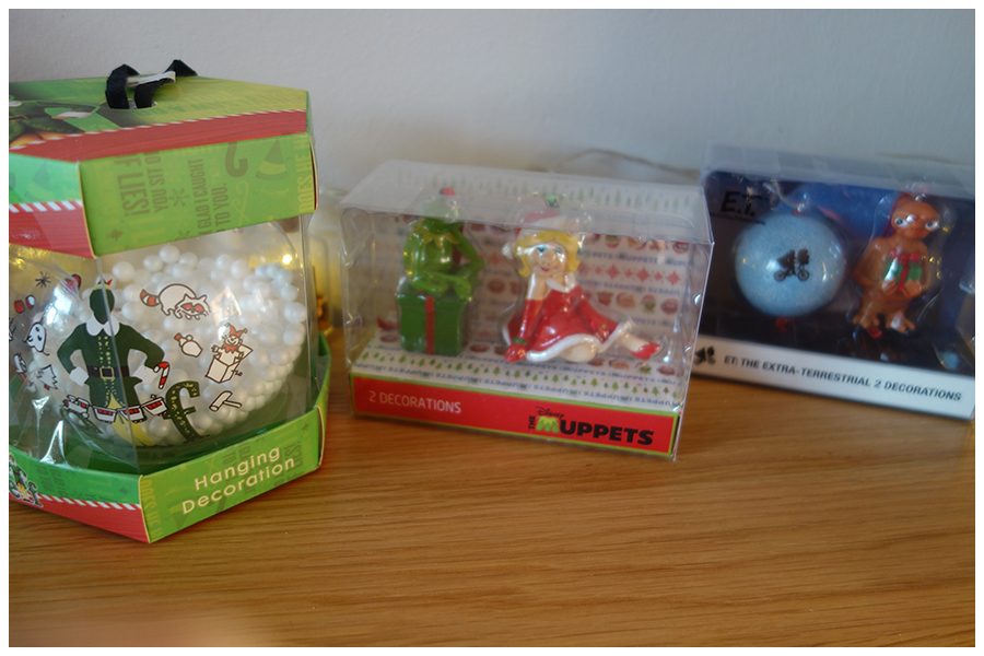The three packs of decorati9ns, the elf bauble which is clear glass with polystyrene balls to look like snow, a two pack of Muppets ones with Miss Piggy and Kermit dressed for Christmas, and a two pack of Christmas ET and a blue moon bauble with their silhouette on