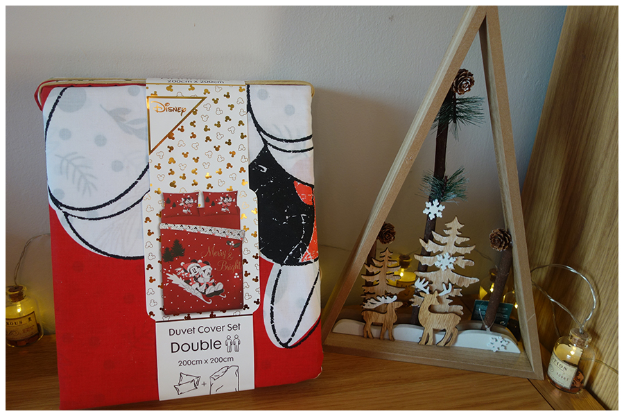 On the left is a pack of Mickey and Minnie Mouse bedding, it sh9ows a pi0cture of the one side that's red with Mickey and Minnie on a sledge with Merry and Bright written on it. On the right is a wooden decorati9n showing a scene with snow, trees and deer cut out of wood and layered with lights behind