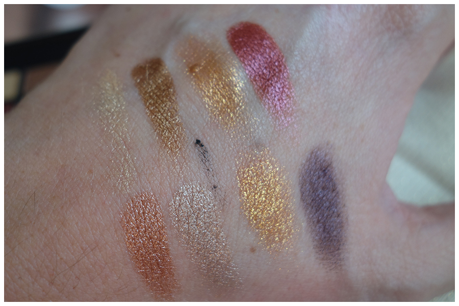 Swatches of the eight eyeshadow colours in the palette. It's a range of metallic shades, mainly golds and creams with a cranberry red and a gunmetal