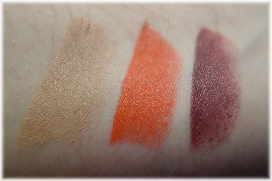 Swatches of the three lipsticks, the nude, orange red and deep purple berry