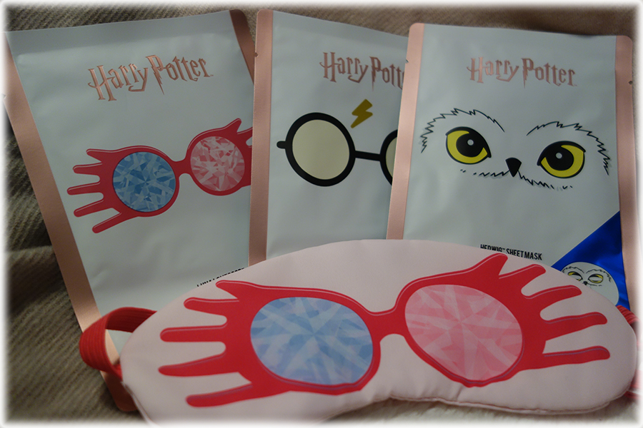 A photo with the three sheet masks along the back, the designs are Luna Lovegood's glasses, Harry Potter's glasses and scar and Hedwig the owl. In front of that is an eye mask with Luna's glasses and a pink background