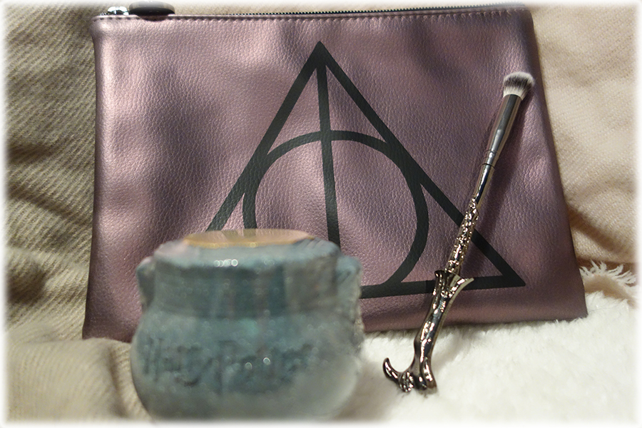 Three of the products from the set. There's the makeup back that's a metallic grey purple with a black deathly hallows symbol on it, a cauldron shaped bath fizzer and the gunmetal grey Voldemort wand eyeshadow brush