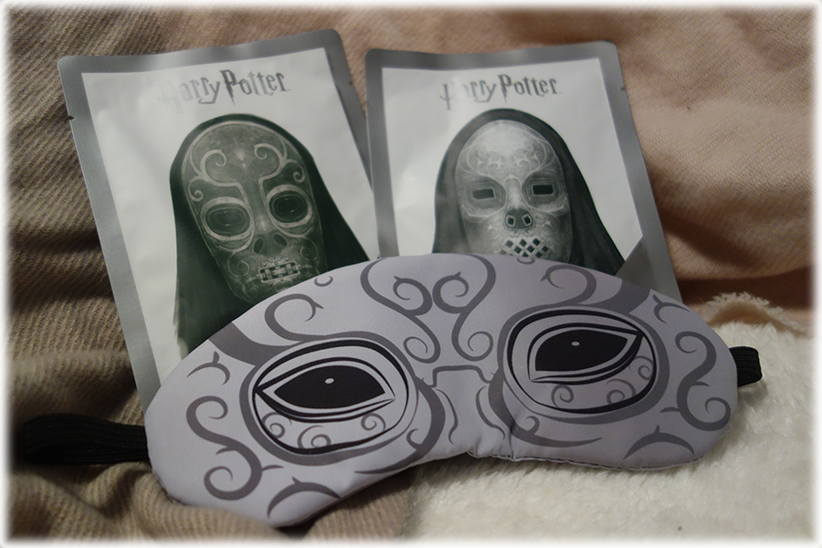 The two sheet masks with images of Death Eaters on the front. In front is the eye mask with a similar design in grey and black on it.