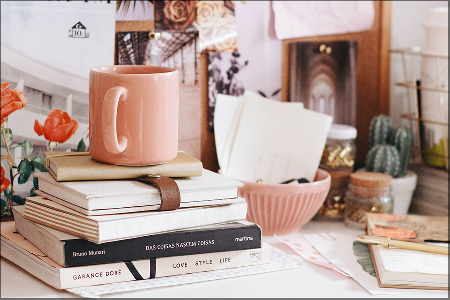 A photo of a light pink mug on a pile of books with more clutter around on a desk