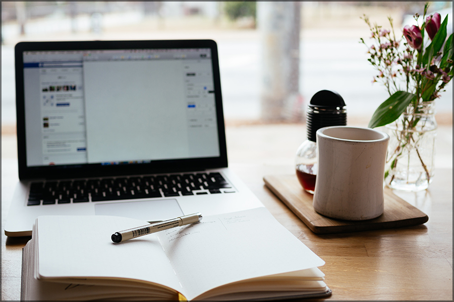 A photo of a laptop on a desk with mug and notebook and pen