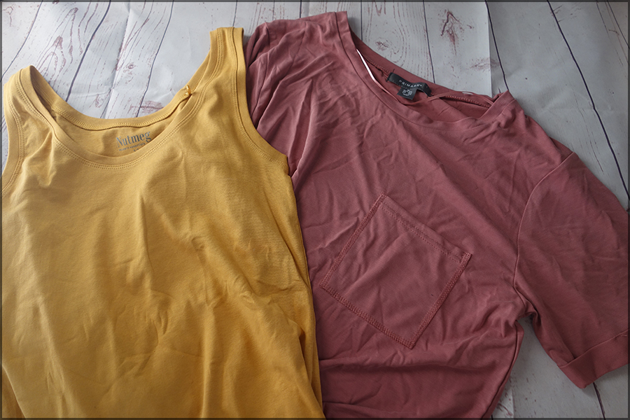 On the left is a mustard sleeveless top with thick straps. On the right is a dusty pink t-shirt with a pocket on the chest and rolled up sleeves.