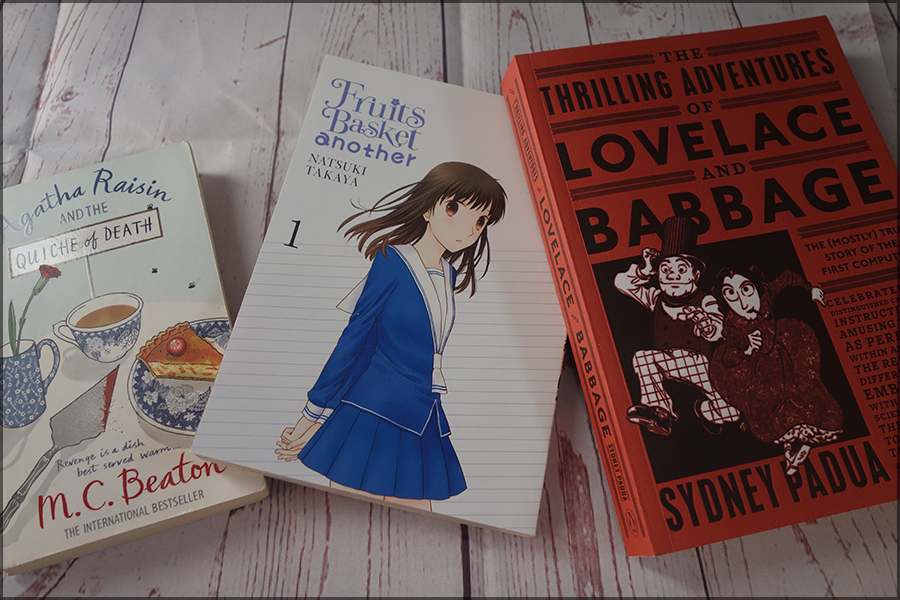 There are three books. From left to right: Agatha Raisin and the Quiche of Death, Fruits Basket Another (the first books) and The Thirlling Adventures of Lovelace and Babbage