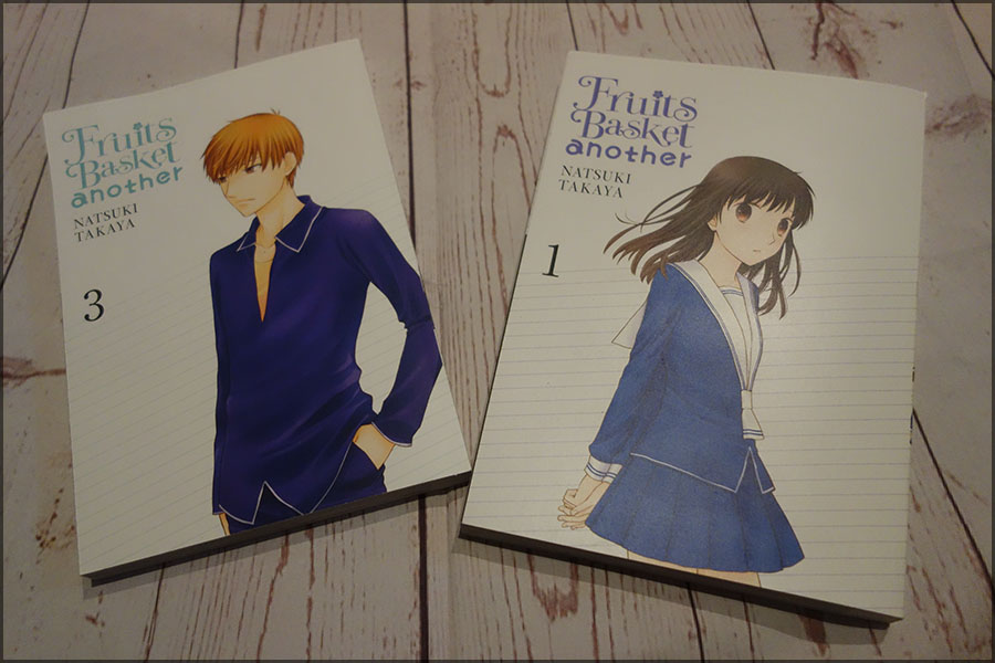 The front covers of the first and third Fruits Basket Another manga. There is a girl with brown hair on the first and a boy with orange hair on the third